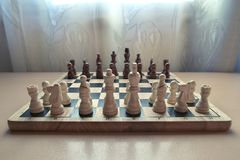 Retro style wooden material chessboard with chess pieces set ready for strategic mind game. royalty free stock photography