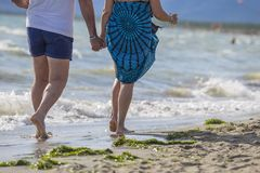Image of a couple of people strolling on the beach holding hands royalty free stock photos