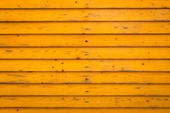 Horizontal old wood fence background. Old wooden planks with yellow paint. Horizontal old wood fence background. Old wooden planks with bright yellow paint stock photo