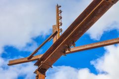 Orange steel girders with blue sky. Horizontal orange steel girders with shadows in front of blue sky and clouds Royalty Free Stock Images