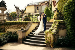 The horizontal outdoor portrait of happy hugging newlyweds standing on the stairs of the beautiful castle. Prague. The horizontal outdoor portrait of happy Royalty Free Stock Photo