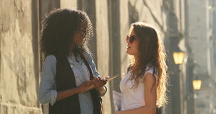 The horizontal outdoor view of the two beautiful multicultural students talking during the sunny day. The horizontal outdoor view of the two beautiful stock footage