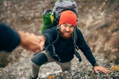 Horizontal outdoors image of traveler bearded man trekking and mountaineering during his journey. Hand of a friend helping the young tourist male hiking in stock image