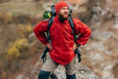 Horizontal shot of young male hiking in mountains wearing red clothes, looks away. Traveler bearded man relaxing after trekking. Horizontal outdoors shot of stock image