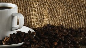 Horizontal pan from coffee maker to cup of espresso with coffee beans on burlap sack fabric. Background stock video footage