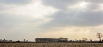 Horizontal panorama of European arable fields on which tractor rides, and in the distance seen a windmill and houses Royalty Free Stock Photos
