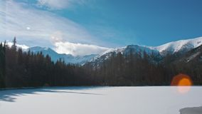 Horizontal Panorama of Lake in Mountains with Snow, Sun Flare and Blue Sky. Horizontal Panorama of Lake in Mountains with Snow and Beautiful Sun Glare and Blue stock video