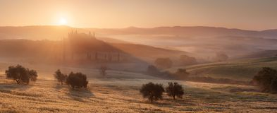Golden Rays in Tuscany. Horizontal panoramic photo of sunset in Tuscany, Italy. The very famous Belvedere manor is visible stock photos