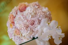 Classy floral arrangement in a pastel round bouquet featuring pink hydrangea roses and orchids. Horizontal perspective of a classy floral arrangement in a pastel stock image