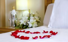 Romantic setup with honeymoon bed with focus on the heart-shaped rose petals royalty free stock photo
