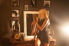 Horizontal photo of adorable girl sitting on the nightstand next Stock Image