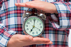 Horizontal photo of an alarm clock in hands on a background of p Stock Images