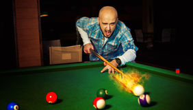Horizontal photo angry man hits fireball at pool billiard Royalty Free Stock Photos