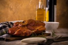 Big piece of smoked pork meat on vintage cutting board. Horizontal photo with big piece of smoked pork meat with bone placed on cutting board. Blue towel Stock Images