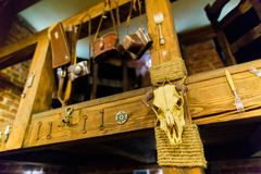The horizontal photo of the bull skull hanging on the wooden stairs decorated with keys, forks and pouches for cameras. In the cafe Stock Photography