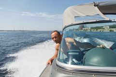 Captain driving a boat on a river. Horizontal photo of a captain driving a boat on a river Stock Photo