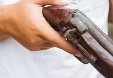 Horizontal photo of closeup hand holding old gun, selective focu. S on the gun Stock Photos
