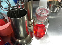 Horizontal photo of closeup surgical scissors red water in bottl. E glass and sterile jar in the emergency room Stock Photo