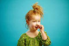 Horizontal photo of cute redheaded girl picking her nose on isolated blue background, has a beautiful face. Young kid in funny situation Royalty Free Stock Photo