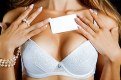 Horizontal photo of female boobs in bra and empty name tag Royalty Free Stock Photography