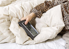 Alarm clock in female hand while in bed Royalty Free Stock Image