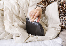 Female hand turning off alarm clock while in bed Stock Images