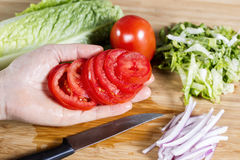 Female hand holding fresh sliced tomato Stock Photo