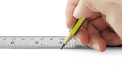 Horizontal photo of female hand using ruler and pencil on white Royalty Free Stock Image