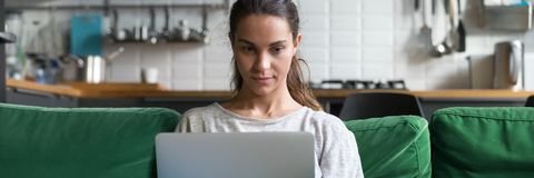 Horizontal photo mixed race female sitting on couch using computer stock image