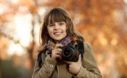 Happy girl outdoor. Horizontal photo, happy beautiful little girl with photocamera, autumnal portrait royalty free stock image