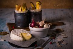 Hot melted camembert cheese on wooden board with onion and fried potatoes Royalty Free Stock Images