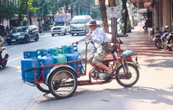 Bangkok, Thailand - October 2017: Male Thai transporting Bottled Gas with motorcicle in busy street of Bangkok. Horizontal photo of male Thai transporting stock photography