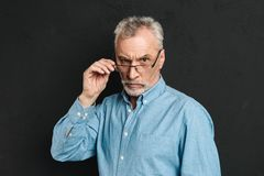 Horizontal photo of mature unshaved man 60s with grey hair weari. Ng eyeglasses looking on camera with severe gaze and touching eyeglasses isolated over black Royalty Free Stock Photography