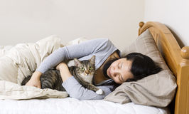Mature woman holding cat while lying in bed Royalty Free Stock Image