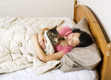 Mature woman looking at her cat while trying to sleep Royalty Free Stock Photo