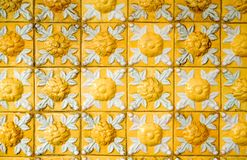 Old and dirty bright yellow relief tiles with floral pattern. Vintage glazed ceramic tiles texture and background. Horizontal photo of old and dirty bright stock images