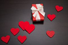 Present for Valentine`s day, Mother`s day or Wedding, wrapped in red paper, white bow and red hearts. Royalty Free Stock Image