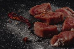 Horizontal photo of raw pork tenderloin meat. Raw meat is on rustic dark baton board, with pepper and salt stock image