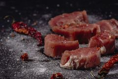 Horizontal photo of raw pork tenderloin meat. Raw meat is on rustic dark baton board, with pepper and salt royalty free stock photos