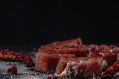 Horizontal photo of raw pork tenderloin meat. Raw meat is on rustic dark baton board, with pepper and salt stock photography