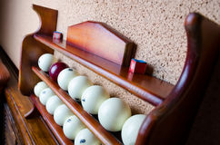 Horizontal photo of Set of balls for a game of pool billiards on shelves. Pool billiard game. Stock Photos