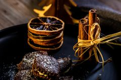 Few cinnamon sticks on black plate with chocolate sweets and dry orange rings royalty free stock images