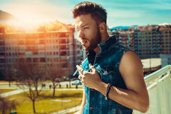 Horizontal photo of sexy male fashion model with cigarette Royalty Free Stock Image