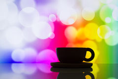 Horizontal photo of silhouette coffee cup on colorful bokeh back Stock Photos