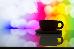 Horizontal photo of silhouette coffee cup on colorful bokeh back Stock Image