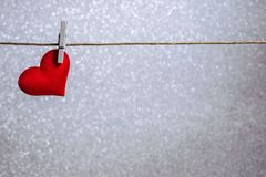 Single red heart hanging from string by clothes peg on silver background. Romantic Valentine`s Day scene with copy space. Horizontal photo of a single red heart stock photography