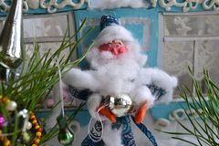 Portrait of the plasticine Father Frost with New Year tree ball and pine. Horizontal photo of small Santa Claus in the blue costume with toy for New Year tree Royalty Free Stock Photo