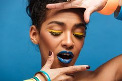 Horizontal photo of stylish mulatto woman with colorful makeup a. Nd curly hair in bun holding hands close to face isolated over blue wall Royalty Free Stock Image
