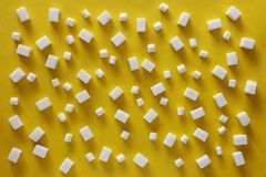 Sugar cubes and marshmallows on yellow background stock photos