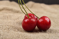 Horizontal photo of tree red cherries with water drops which are together on one green branch on jute on a table. Selective focus. Stock Photo